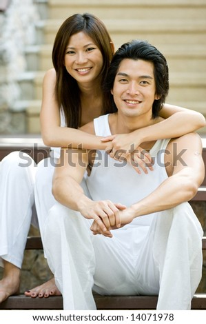 A young couple sitting together on vacation - stock photo