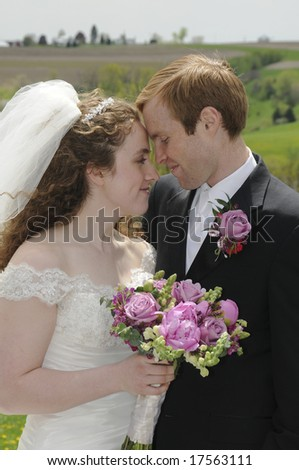 A young couple spends a quiet moment together in front of a Wisconsin farm field on their wedding day - stock photo