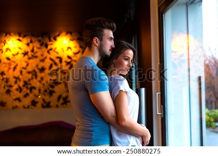 A young couple standing at home at the window while hugging in love.  - stock photo
