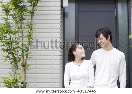 A young couple standing in front of the house - stock photo
