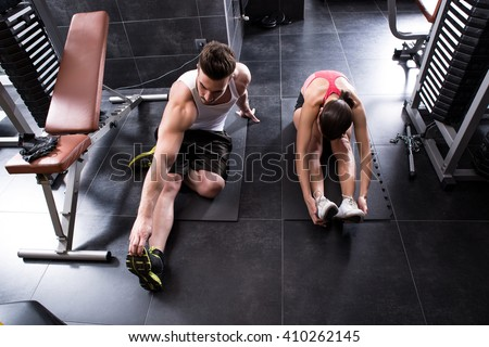 A young couple stretching in the gym - stock photo