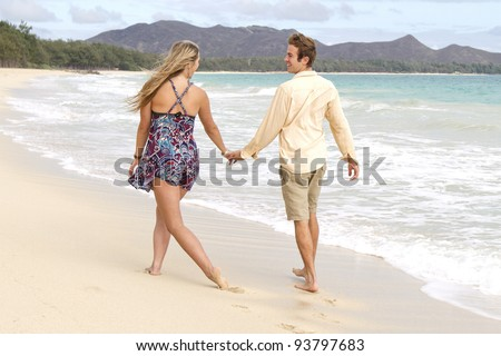A young couple stroll down the beach playfully. - stock photo