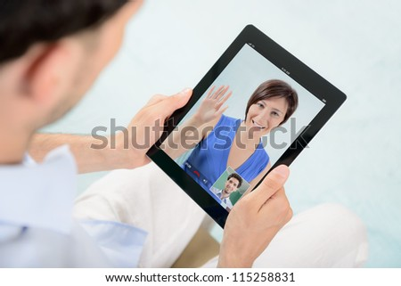 A young couple talking to each other via online video chat. - stock photo