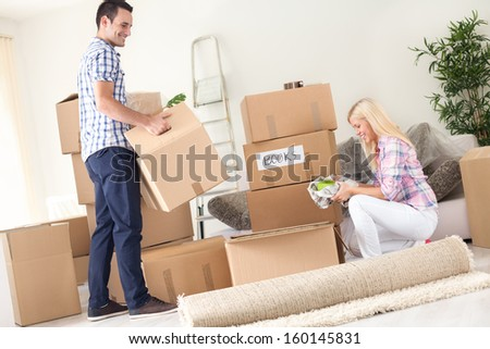 A young couple unpack moving boxes. - stock photo
