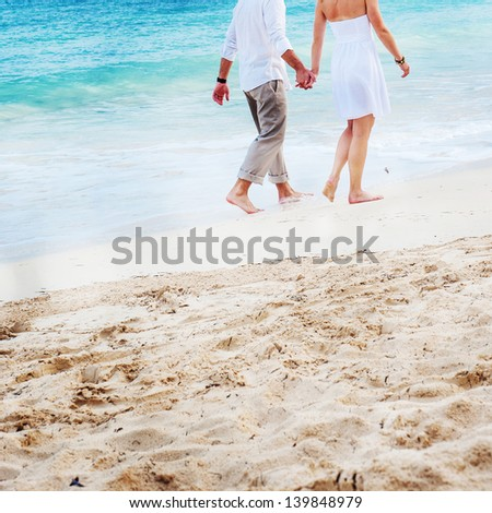 A young couple walking hand in hand on a Mexican beach. - stock photo