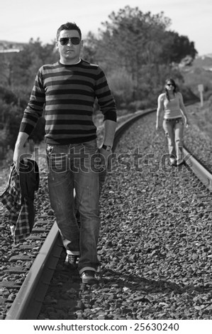 A young couple walking on a railway track (Black and White photo) - stock photo