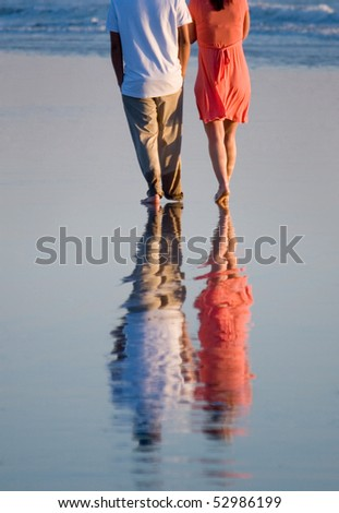 A young couple walking on the beach - stock photo