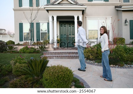 A young couple walking up to their new home - stock photo