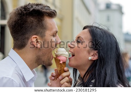 a young couple with a bag of ice. ice cream cones as a refreshment in summer - stock photo