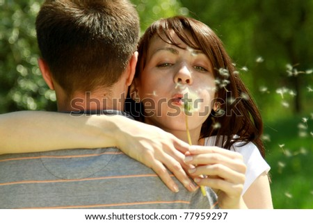 A young couple with a dandelion - stock photo