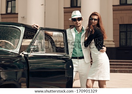 A young couple with a retro car - stock photo