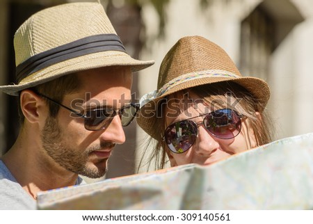 a young couple with hats , looking at a map