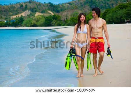 A young couple with snorkeling gear on a tropical beach