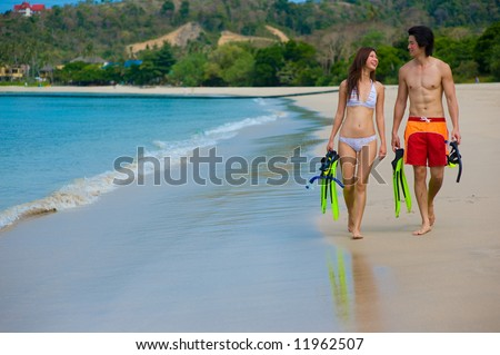 A young couple with snorkelling gear on a tropical beach - stock photo