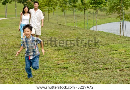 A young couple with their young son running by a lake - stock photo