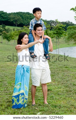A young couple with their young son walking by a lake - stock photo