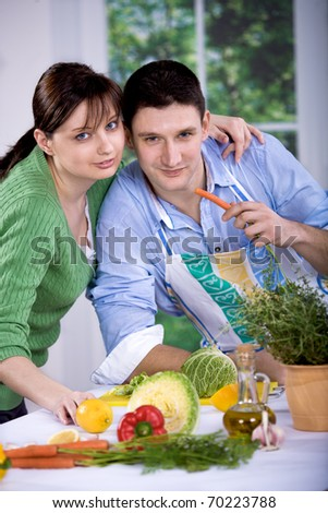 a young couple working in the kitchen - stock photo