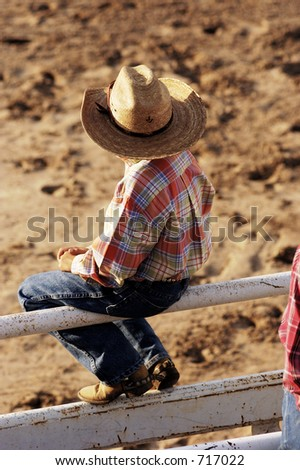 A young cowboy watches the rodeo action. - stock photo