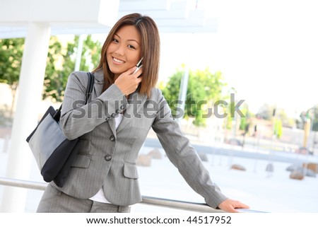 A young cute asian business woman at her office building on phone - stock photo