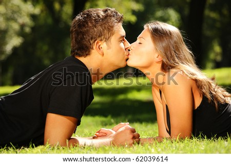 A young cute couple lying on the grass in the park and kissing - stock photo