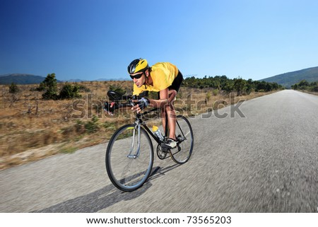 A young cyclist riding a bike on an open road - stock photo