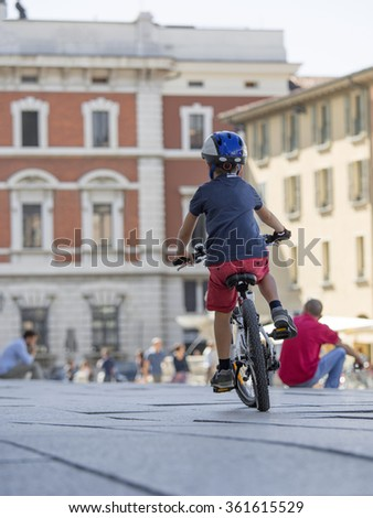 A young cyclist with helmet pedals in the city center , Brescia , Italy. - stock photo