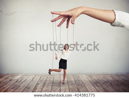 A young dark-hear woman in white blouse and black skirt is moving like a puppet while big hand above her is pulling the strings