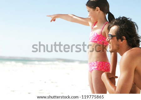 A young daughter points into the distance showing something to her father who is kneeling at her sideat beach - stock photo