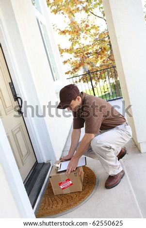 A young delivery man delivering a package to a house - stock photo