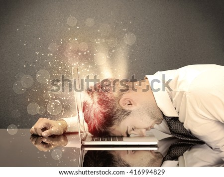 A young depressed business person laying his head on computer keyboard with thoughts exploding from his head illustrated by light beams concept - stock photo
