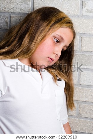 A young depressed girl is leaning her head against some bricks - stock photo