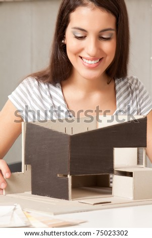 A young design student or architect building a house model - stock photo