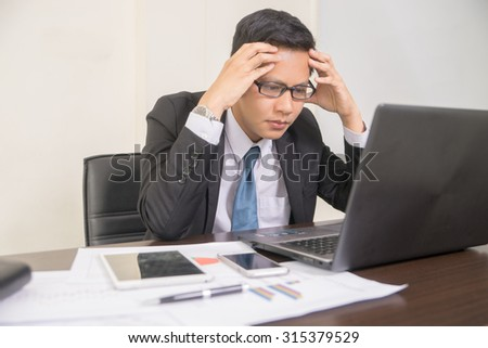 A young desperate businessman Portrait of a stressed manager in office - stock photo