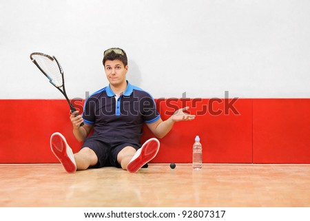 A young disappointed squash player holding a broken racket in a squash court - stock photo