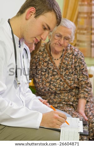 A young doctor evaluating the electrocardiogram at the home of an elderly woman. - stock photo
