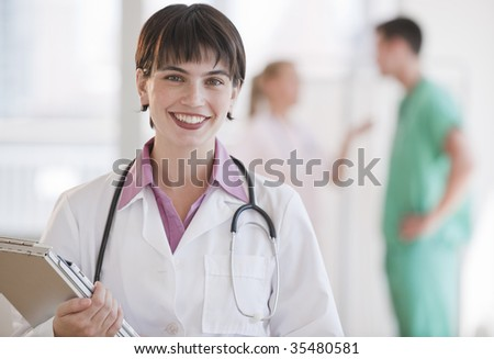 A young doctor is smiling at the camera.  Horizontally framed shot.