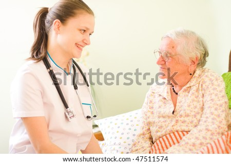 A young doctor / nurse visiting an elderly sick woman socialising - talking - with her. - stock photo