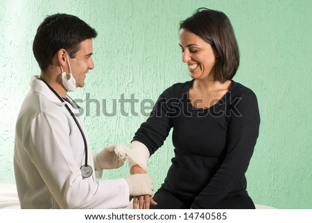 A young doctor, standing, wraps a patient's arm with tape. - horizontally framed - stock photo