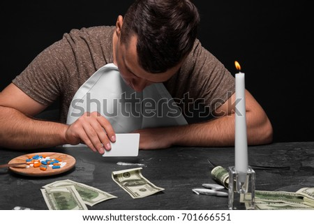 A young drug addict on a black background. A junkie with cash, drugs, and candles sitting at the table. Copy space.