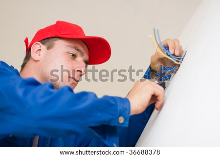 A young electrician insulating electric wires of an electric box. - stock photo