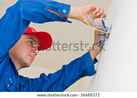 A young electrician insulating the wires of an electric box. - stock photo