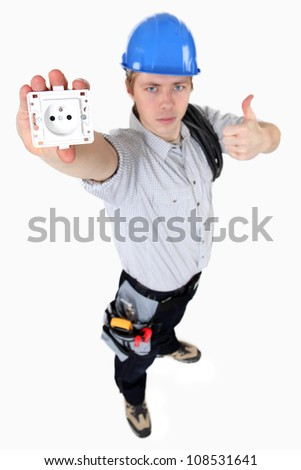 A young electrician showing an outlet. - stock photo