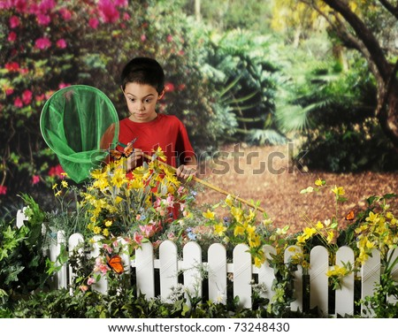 A young elementary boy catching butterflies in a beautiful garden.  He's looking wide-eyed as a monarch comes in close. - stock photo