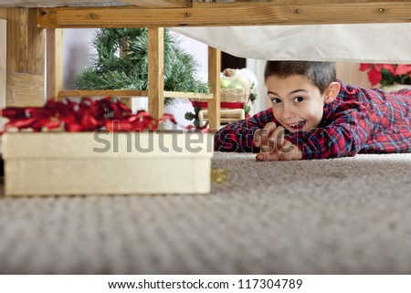 A young elementary boy delighted at seeing a boxed gift under his parents' bed. - stock photo