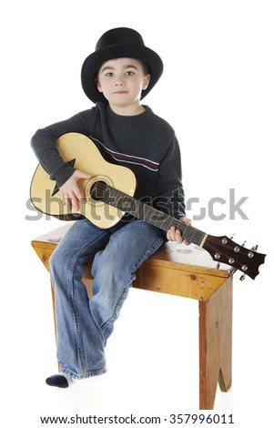 A young elementary boy playing a guitar while wearing a black top hat.  On a white background.