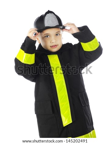 A young elementary boy putting on his chief's hat while wearing his fireman's coat.  On a white background. - stock photo