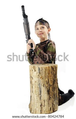 """A young elementary """"soldier"""" in army camouflage, poised with his machine gun behind an old tree stump.  Isolated on white. - stock photo"""