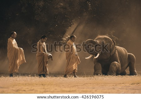 A young elephant  and monk at Surin in Thailand ,sepia image