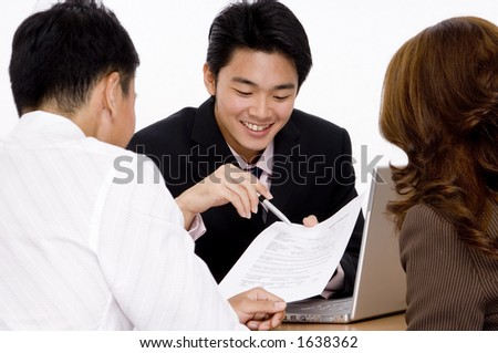 A young employee helps a couple with a form - stock photo