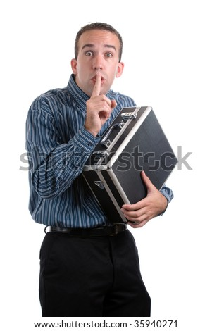 A young employee is sneaking away a case of private documents and telling the viewer to be quiet, isolated against a white background - stock photo